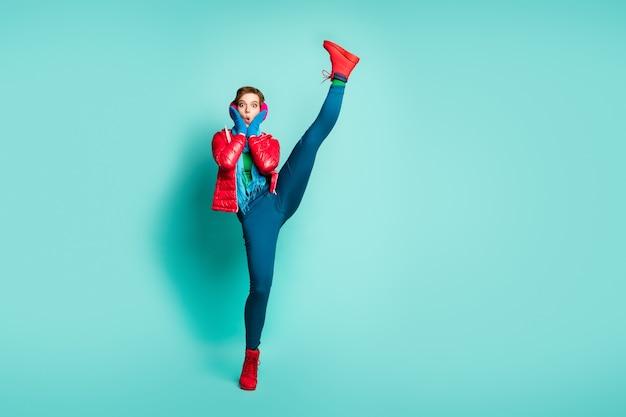 Ganzkörperfoto der lustigen dame heben bein hoch unglaubliche flexibilität nach dem ersten training im fitnessstudio tragen rote mantelhandschuhe rosa ohrenschützer hosen schuhe isoliert blaugrün farbe wand