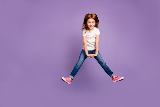 Ganzkörperfoto der lustigen kleinen ingwerdame, die hoch springt und sich in der luft freut
