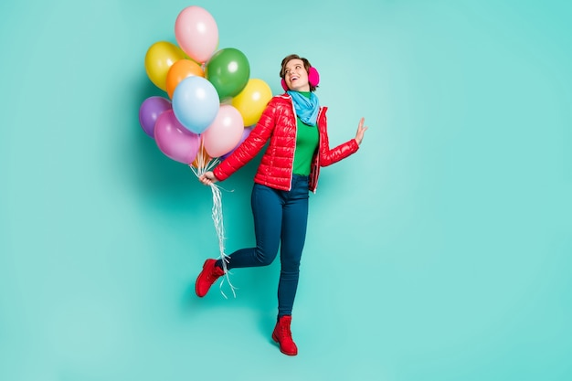 Ganzkörperfoto der lustigen kühlen dame kam geburtstagsfeier bringen viele bunte luftballons tragen lässig roten mantel schal rosa ohrenschützer hosen schuhe isoliert blaugrün farbe wand