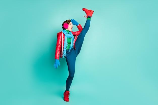 Ganzkörperfoto der lustigen sprachlosen dame heben bein hoch coole flexibilität blick weit weg lange straße tragen rote mantelhandschuhe rosa ohrenschützer hosen schuhe isoliert blaugrün farbe wand