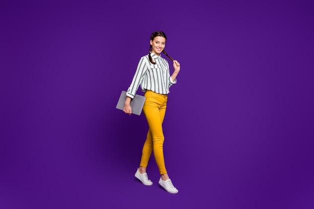 Ganzkörperfoto der schönen geschäftsdame, die notebookhände hält, die studenten vortragsklasse tragen gestreifte gelbe hose des gestreiften hemdes lokalisierten lila farbhintergrund tragen