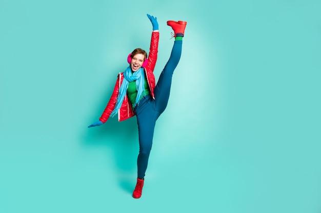 Ganzkörperfoto der verrückten dame heben bein hoch hoch demonstrierend schockierende flexibilität party performer tragen rote mantelhandschuhe rosa ohrenschützer hosen schuhe isoliert blaugrün farbe wand