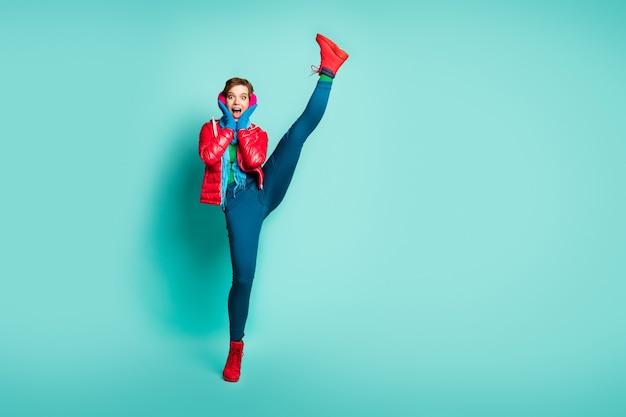 Ganzkörperfoto der verrückten schreienden dame heben bein hoch hohe schockierende flexibilität nach dem ersten training im fitnessstudio tragen rote mantelhandschuhe rosa ohrenschützer hosen schuhe isoliert blaugrüne farbe wand