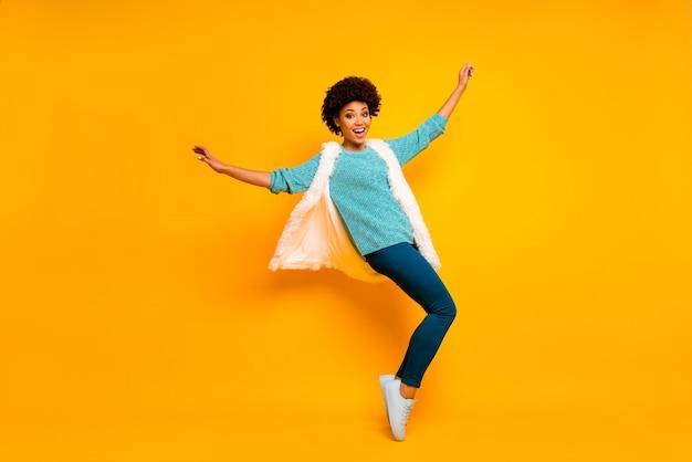 Ganzkörperfoto des fröhlichen lustigen lustigen afroamerikanischen mädchens genießen tanzherbstfeiertage emotionen erhöhen hände tragen weiße blaue flauschige weste hosen glänzen isoliert helle farbe wand