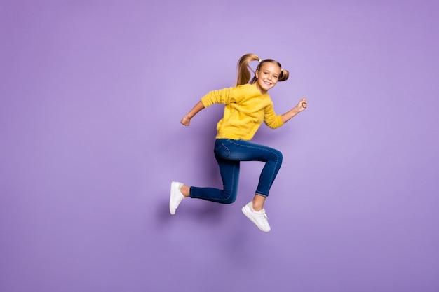 Ganzkörperfoto des fröhlichen süßen kindersprunglaufs nach schwarzen freitagschnäppchen tragen lässige artkleidung, die über lila farbwand isoliert wird