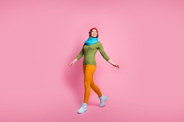 Ganzkörperfoto des fröhlichen zufriedenen mädchens gehen spazieren genießen winterferien tragen modernen schuhpullover isoliert über pastellfarbener wand