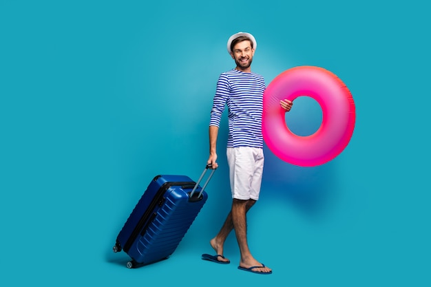 Ganzkörperfoto des gutaussehenden reisenden halten rolling case rund großen rosa rettungsring ankommen sonne land tragen gestreifte matrosenhemd mütze shorts flip flops isoliert blaue farbe