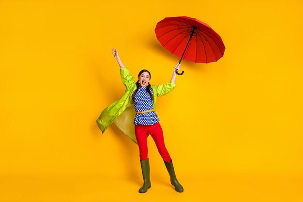 Ganzkörperfoto eines aufgeregten, energiegeladenen mädchens mit rotem sonnenschirm, luftfliege, wind, gutes aussehen, outfit, gummischuhe, einzeln auf hell glänzendem hintergrund