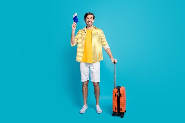 Ganzkörperfoto eines aufgeregten verrückten touristen genießen grenzen offene kovid-quarantäne-reisen ins ausland halten tickets gepäck tragen gut aussehende kleidung einzeln auf blauem hintergrund
