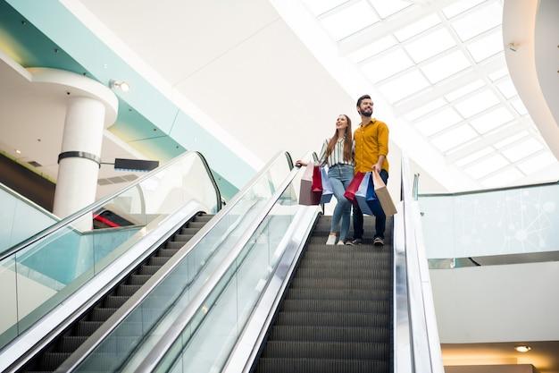 Ganzkörperfoto von hübscher dame, gutaussehendem mann paar verbringen freizeit shopping mall umarmen viele taschen tragen rolltreppe gute laune tragen lässig jeanshemd schuhe outfit drinnen tragen