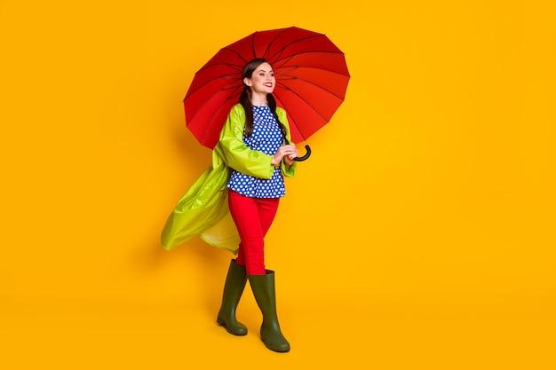 Ganzkörperfoto von positivem, fröhlichem mädchen genießen frühlingswetter halten roten sonnenschirm tragen gut aussehende kleidung gummischuhe einzeln auf hell glänzendem hintergrund