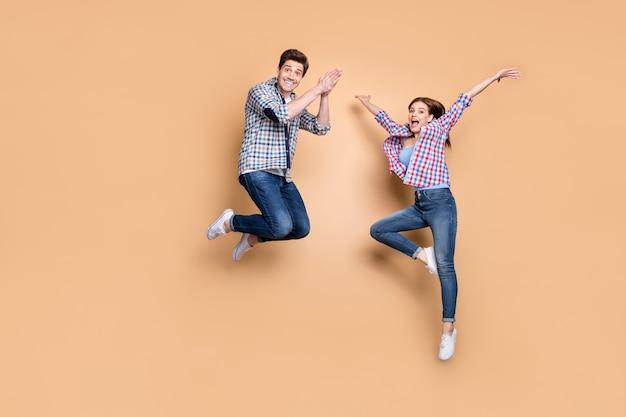 Ganzkörperfoto von zwei menschen verrückte dame kerl hoch springen genießen sommerzeit am ersten wochenende tragen lässige karierte jeans kleidung isoliert beige farbe hintergrund