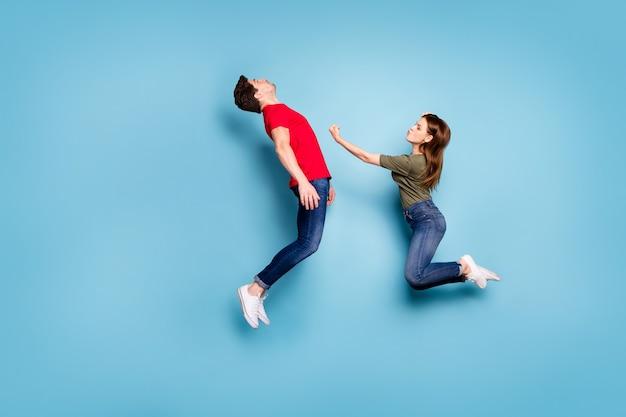Ganzkörperfoto von zwei verheirateten menschen starke frau trittmann fällt im knockout sie sieger im kampf kampf kampfsprung tragen grün rot t-shirt jeans jeans isoliert blau farbe hintergrund