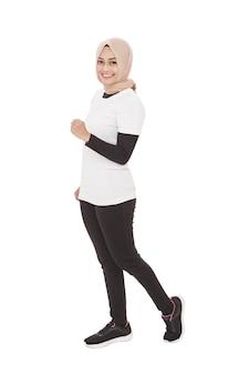 Ganzkörperporträt der asiatischen sportlichen frau, die beim lächeln joggt