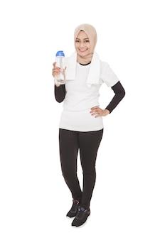 Ganzkörperporträt der asiatischen sportlichen frau, die hijab hält, der eine flasche mineralwasser hält