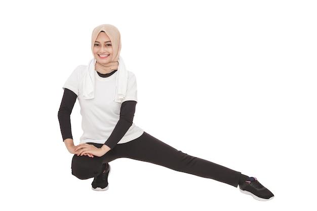 Ganzkörperporträt der muslimischen sportlichen frau, die beinstreckung tut