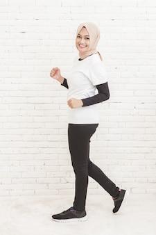 Ganzkörperporträt der schönen asiatischen sportlichen frau, die mit weißem backsteinmauerhintergrund joggt