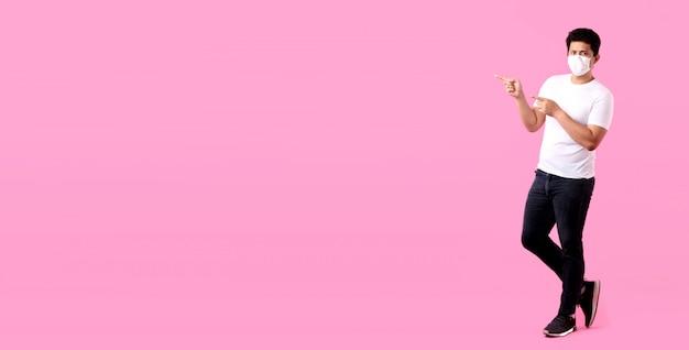 Ganzkörperporträt des gutaussehenden asiatischen mannes, der eine maske trägt, ist krank zeigerfinger lokalisiert auf rosa hintergrund im studio mit kopienraum.
