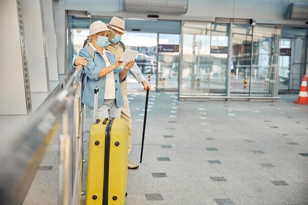 Ganzkörperporträt einer betagten dame und ihres ehepartners, die mit ihrem gepäck am flughafen stehen