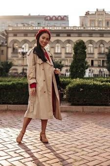 Ganzkörperporträt einer brünetten frau in beigem trenchcoat, rotem barett und kleid lächelt breit und hält die handtasche draußen