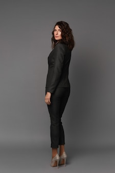 Ganzkörperporträt einer erwachsenen modellfrau mit perfektem körper, der einen dunklen anzug und hochhackige schuhe trägt, die gegen graues oberflächenkonzept von geschäftskleidung für besprechungen und spaziergänge aufwerfen