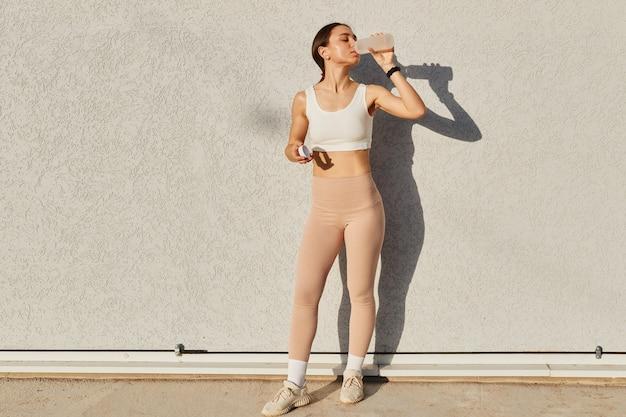 Ganzkörperporträt einer schlanken frau mit perfektem körper, die ein weißes oberteil und beige leggings trägt
