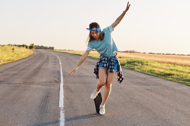 Ganzkörperporträt einer schlanken sportlichen frau, die tricks auf einem skateboard macht, aktive zeit allein verbringt, draußen auf der straße, erhobene arme, mit aufgeregtem gesichtsausdruck nach unten schaut.