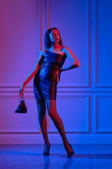 Ganzkörperporträt eines afroamerikanischen modells mit dreieckiger handtasche unter neonlichtern