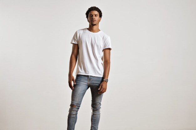 Ganzkörperporträt eines athletischen jungen mannes in zerrissenen hellblauen jeans und leerem weißen kurzarm-t-shirt