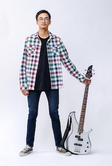 Ganzkörperporträt eines hübschen jungen teenagers, der eine bassgitarre im studio hält. professioneller junger junior-bassist, der isoliert mit weißem hintergrund lächelt und in die kamera schaut