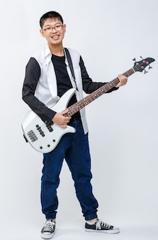 Ganzkörperporträtaufnahme eines netten lächelnden jungen teenagers, der bassgitarre hält. professioneller junior-bassist, der ein instrument steht und spielt, während er in die kamera schaut, isoliert auf weißem hintergrund