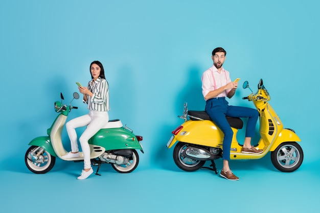 Ganzkörperprofil seitenfoto erstaunt zwei personen frau ehemann fahrer sitzen hubschrauber verwenden handy beeindruckt gps-navigation denken verlorene abendkleidung isoliert blaue farbe wand