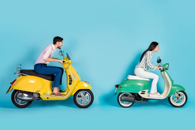 Ganzkörperprofil seitenfoto von energiegeladenen bikern fahren gelbgrüne hubschrauber fahren schnell konkurrieren auf der straße route tragen weiße abendgarderobe hosen hosen isoliert über blaue farbe wand