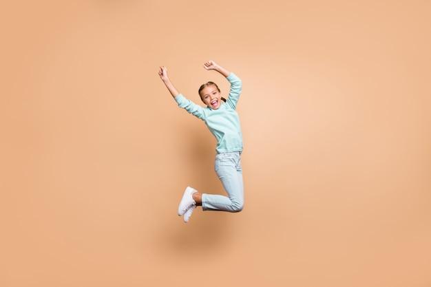 Ganzkörperprofilfoto der schönen lustigen kleinen dame, die hoch oben cheerleader springt, die gewinnende erhöhungsfäuste feiert, tragen blaue pulloverjeansschuhe isolierte beige farbwand