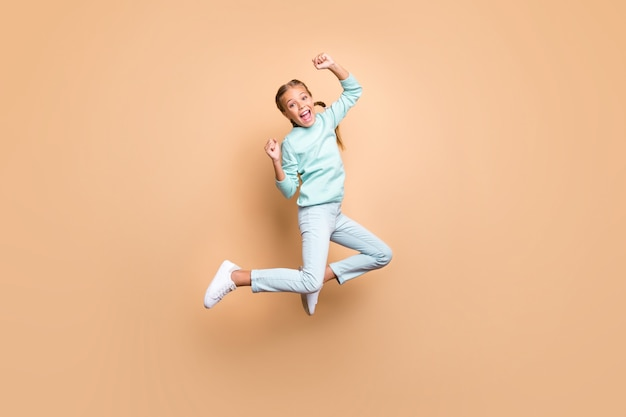 Ganzkörperprofilfoto der schönen lustigen kleinen dame, die hoch oben springt und siegreiche erhöhungsfäuste feiert, tragen blaue pulloverjeansschuhe isolierte beige farbwand