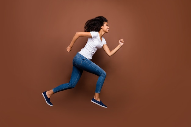Ganzkörperprofilporträt der verrückten lustigen dunklen hautdame, die hohe sportliche wettkampfteilnehmer springt, die schnelles ende tragen, tragen weiße t-shirt jeans.