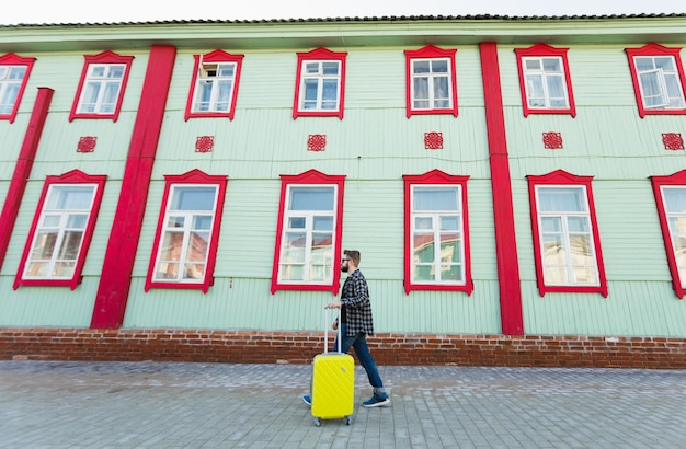 Ganzkörperseitenporträt eines glücklichen reisemannes mit koffer, der am gebäude in der stadt entlang geht