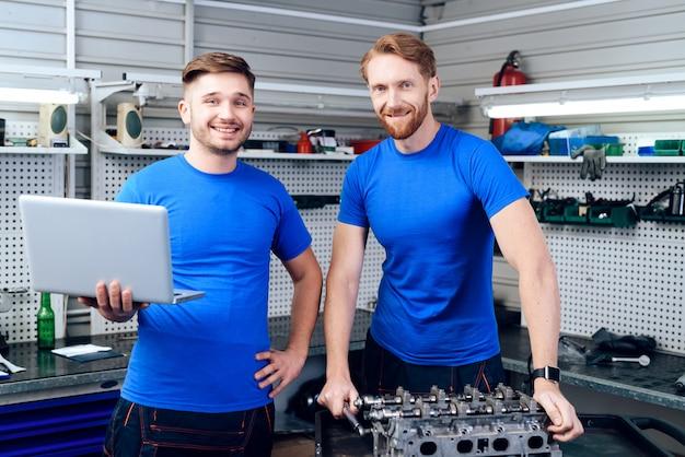 Garage mit zwei junge automechanikern, die konzept aufwirft.