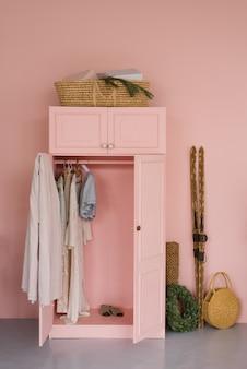 Garderobe mit kleidung, hölzernen retro- skis und weihnachtskranz im rosa wohnzimmer
