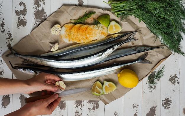Garfish, billfish roh und frisch, draufsicht, mit den zwiebeln, zitrone, vorbereitet für das kochen