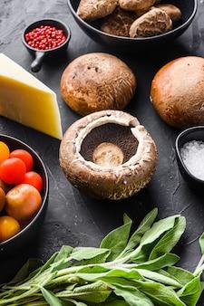 Garlicky portabello pilze zutaten zum backen, cheddar-käse und salbei auf schwarzem hintergrund. seitenansicht. selektiver fokus.