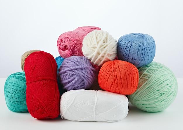 Garn für handarbeit und stricken. auf eine weiße oberfläche stellen