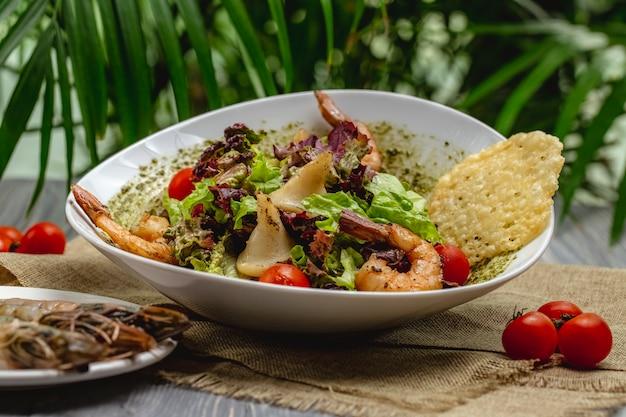 Garnelen-caesar-salat mit kirschtomaten in einem weißen teller auf einem holztisch