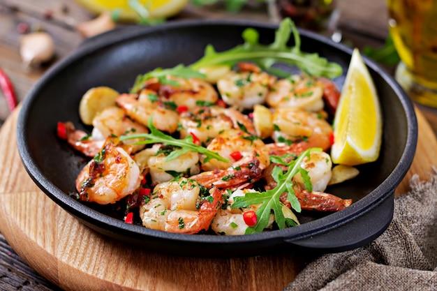 Garnelen shrimps gebraten in knoblauchbutter mit zitrone und petersilie auf hölzernen hintergrund.