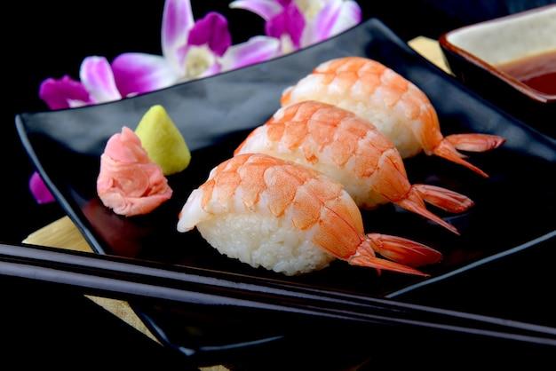 Garnelen-sushi oder japanisches ebi-sushi auf schwarzem teller mit wasabi im blitzlicht.