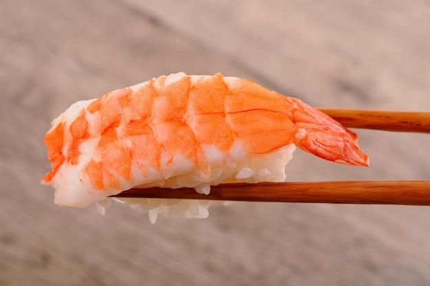 Garnelen-sushi von stäbchen gehalten