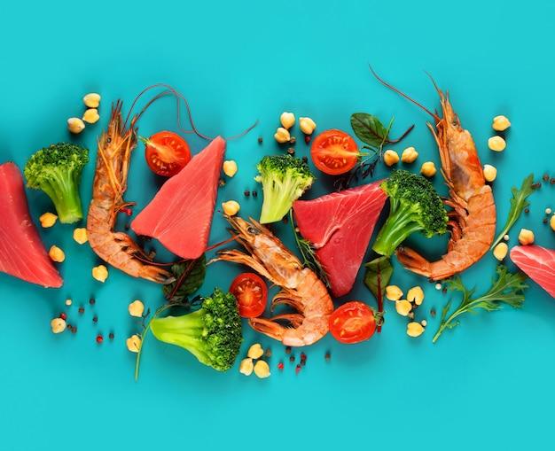 Garnelen, thunfisch, brokkoli, kirschtomaten und kichererbsen auf hellblauem hintergrund. konzept gesunde pescataian-diät. meeresfrüchte, fisch, gemüse. pescetarian und flexsitarian diätplanprodukte. ansicht von oben.