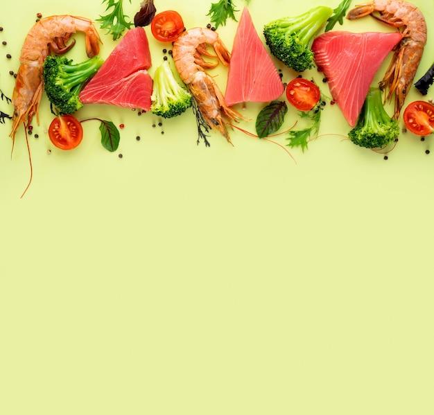 Garnelen-thunfisch-brokkoli-kirschtomaten und spinat auf einem hellgrünen hintergrundkonzept gesund