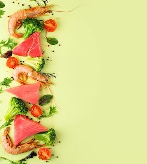 Garnelen, thunfisch, brokkoli, kirschtomaten und spinat auf hellgrünem hintergrund. konzept gesunde pescataian-diät. meeresfrüchte, fisch, gemüse. pescetarische und flexsitäre diätplanprodukte.platz kopieren