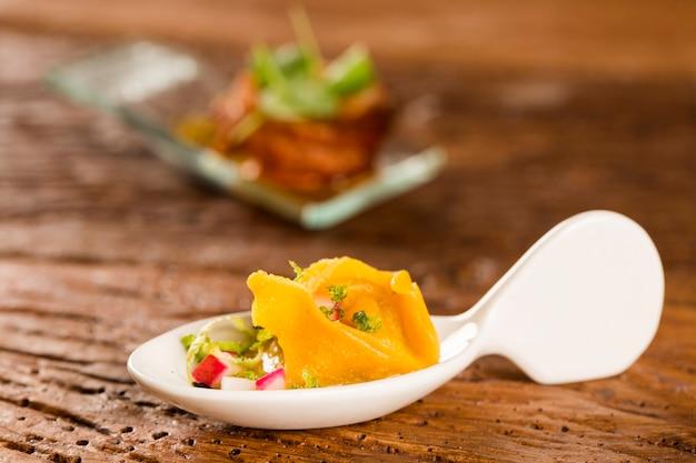 Garnelentortelline, morgensauce, radieschen und schwarzes salz in einem löffel. probieren sie gastronomisches fingerfood